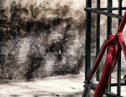 Detalhe de uma bicicleta encostada em um gradil