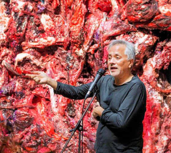Um homem palestra diante a um pedaço de carne